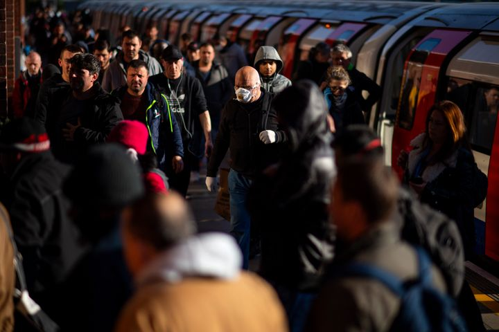 Commuters exit the tube at West Ham station in East London on May 14, 2020.