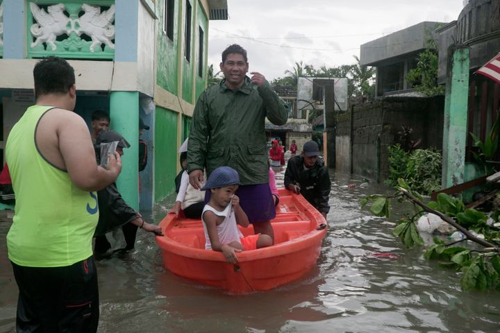 Residents ride a boat along a flooded village as Typhoon Vongfong passes by Sorsogon province, northeastern Philippines, on M