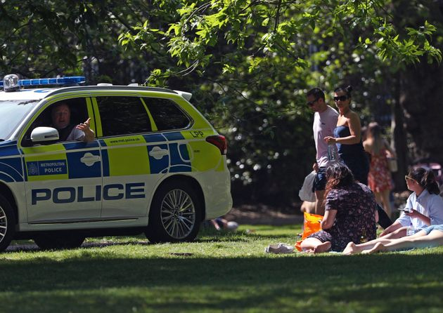Police officers in a patrol car move sunbathers on in Greenwich Park, as the UK continues its lockdown...