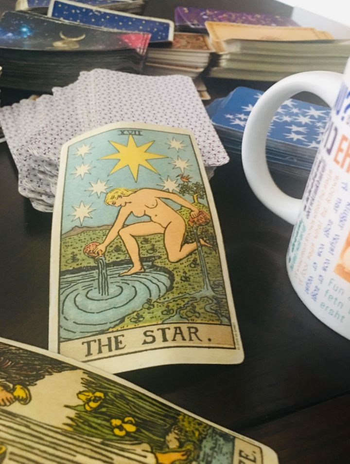 The Star card is displayed among a collection of the author's tarot decks.
