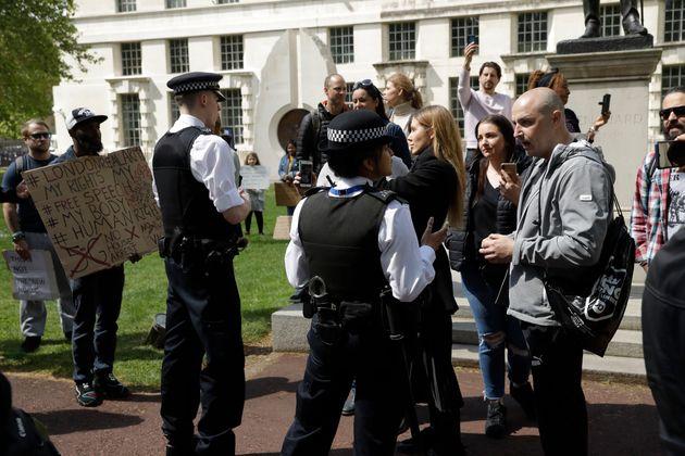 Police officers speak to people taking part in a coronavirus anti-lockdown, anti-vaccine, anti-5G and...