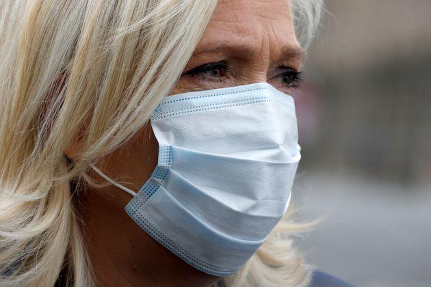 Marine Le Pen, leader du Rassemblement national, portant un masque de protection, participe à...