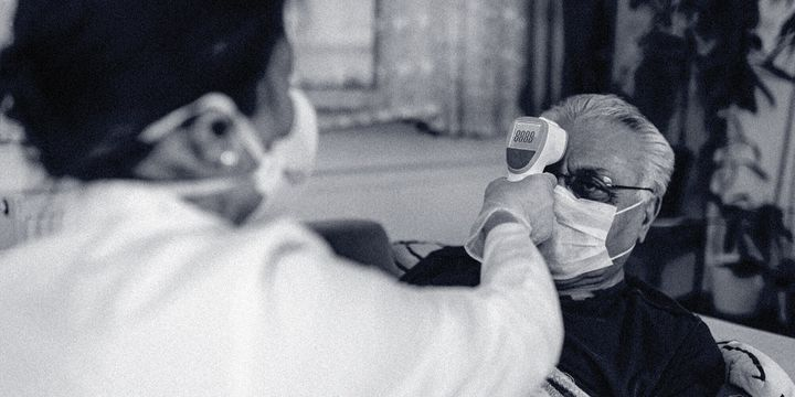 A health worker wearing personal protective equipment takes a person's temperature.