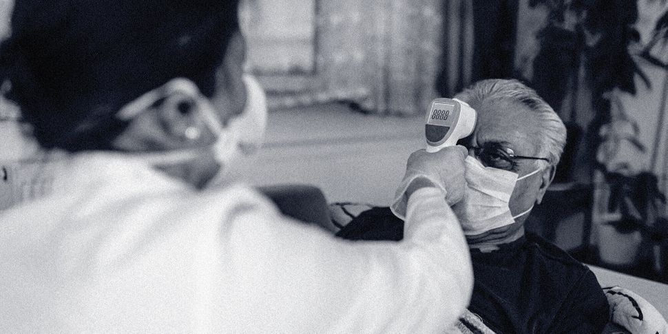 A health worker wearing personal protective equipment takes a person's