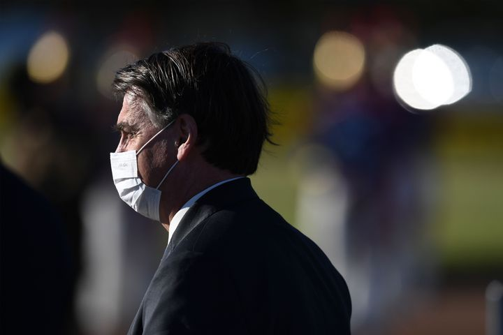 Brazilian President Jair Bolsonaro wears a face mask as he arrives at the flag-raising ceremony before a ministerial meeting