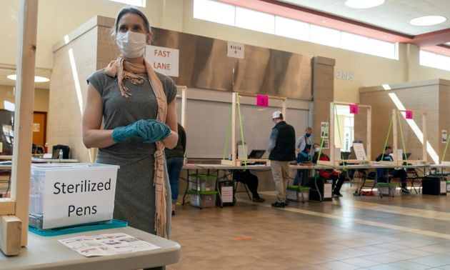 \Poll worker Rhonda Griffin stands ready to hand out sterilized pens at a polling place on April 7, 2020...