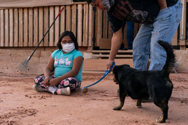 Annabelle Dinehdeal, 8, watches as her father Eugene Dinehdeal, plays ball with their dog Wally on their...