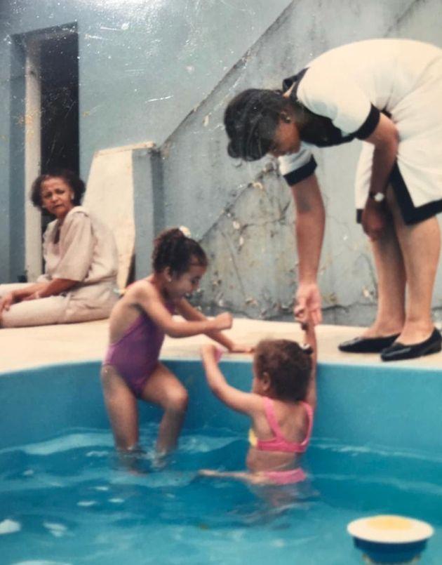 Mãe de Carmen observa a filha brincando com as
