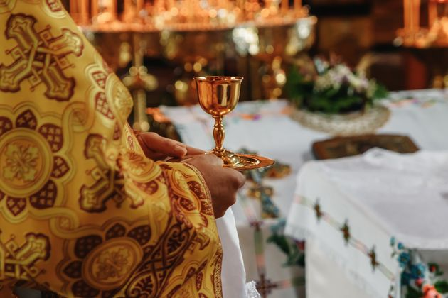 Consecrated bread and wine in chalice on Holy See, during orthodox liturgy on Easter