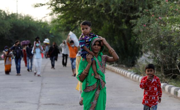 A migrant worker carries her child, as they make their way across the border to their home state of Uttar...