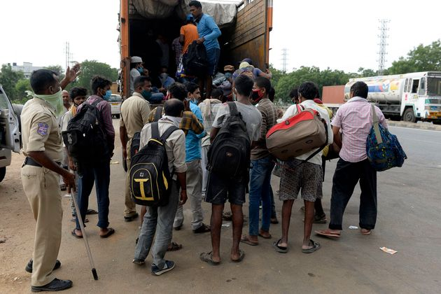 Migrant workers board on a truck to return to their hometowns after the government eased a nationwide...