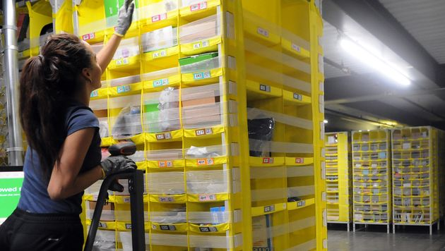 An Amazon associate picks items from a mobile shelving unit at a fulfillment centre in Orlando, Fla.,...