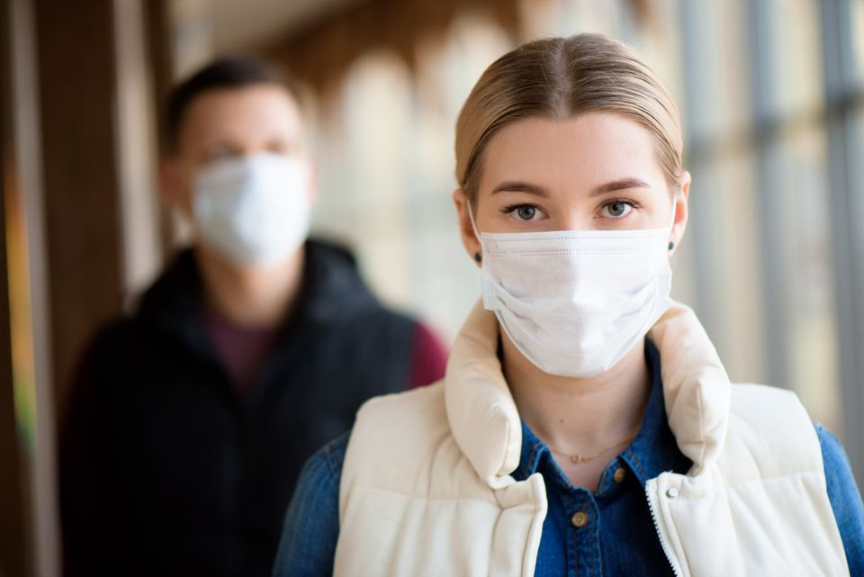 Man and woman wearing protective mask against transmissible infectious diseases and as protection against...