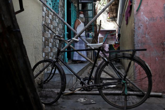 A man stands behind a makeshift barricade set up to stop people from entering a lane, during a nationwide...