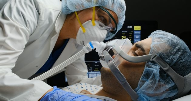 Female caucasian doctor checking on Covid-19 infected patient while connected to a ventilator at a hospital