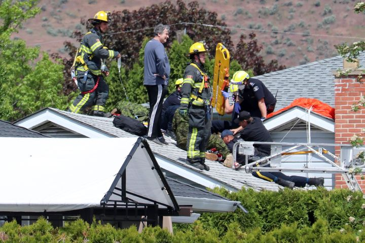 First responders attend to a person on a rooftop at the scene of a crash involving a Canadian Forces Snowbirds aircraft in Kamloops, B.C. on May 17, 2020.