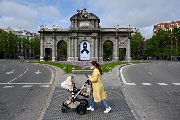 Una mujer pasea con su bebé por la madrileña Puerta de Alcalá durante la
