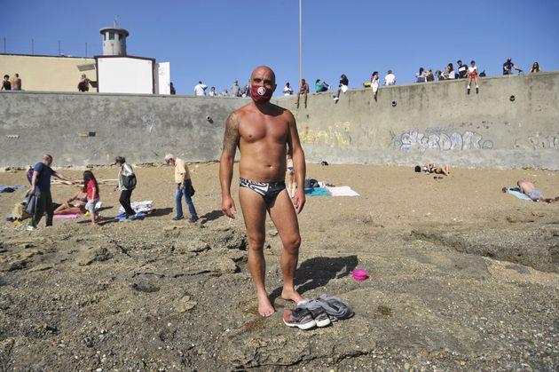 イタリア・リヴォルノ(5月17日)。マスクを着けて日光浴をする男性。