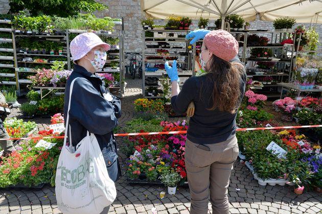 イタリア・トレント(5月17日)。マスクと手袋をつけて立ち話をする女性たち。