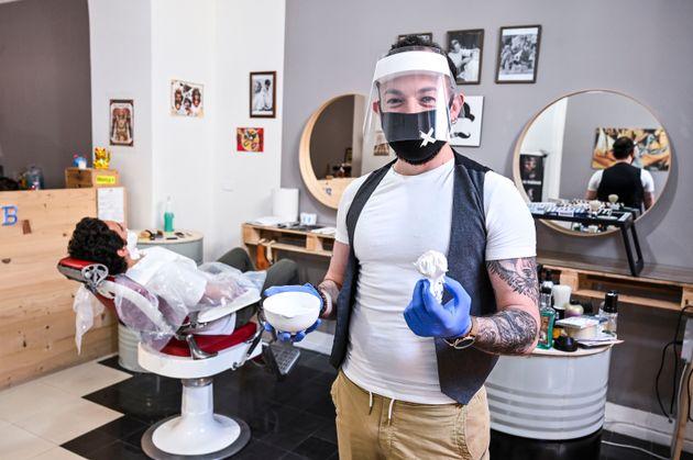 イタリア・カターニア(5月16日)。マスクや透明のバイザーなどを身につけた理容師は、18日の営業再開に向けて手順の確認をしていた。