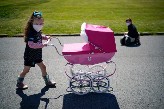 イギリス・バーケンヘッド(5月16日)。マスクをつけることが「ニュー・ノーマル(新しい常識)」となる中、マスクをつけた少女が人形を乳母車に入れて公園を散歩していた。