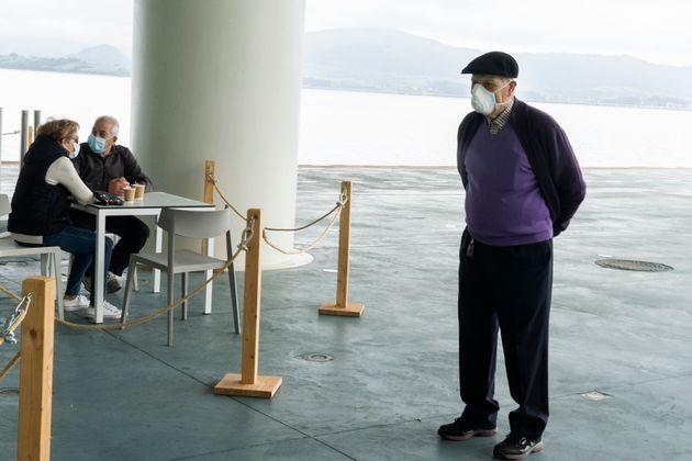 スペイン・サンタンデール(5月12日)。営業を始めた飲食店ではテーブルや客の数に制限があり、この男性は自分の入店の順番を待っている。