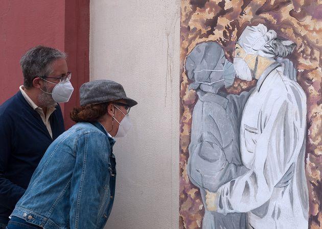 スペイン・マラガ(5月15日)。マスクをつけた看護師がキスする姿を描いた絵を見る、マスクをつけた人たち。
