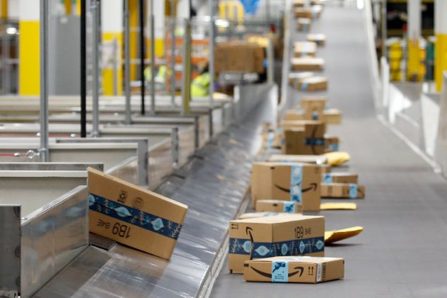 In this Dec. 17, 2019, file photo, Amazon packages move along a conveyor at an Amazon warehouse facility...