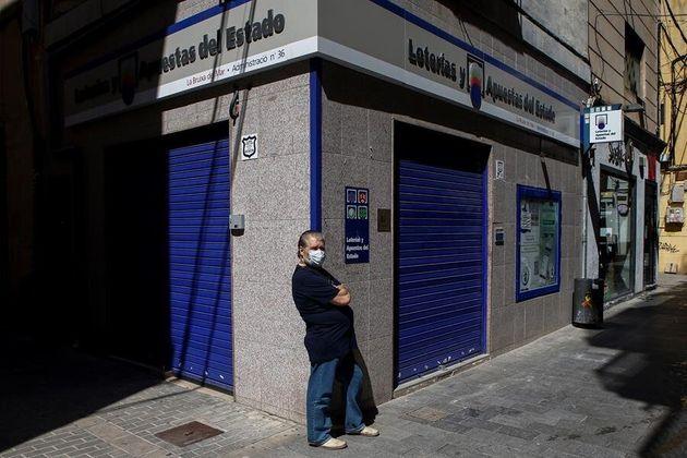 Un ciudadano transita frente al edificio de una administración de lotería en la calle del Mar de Badalona