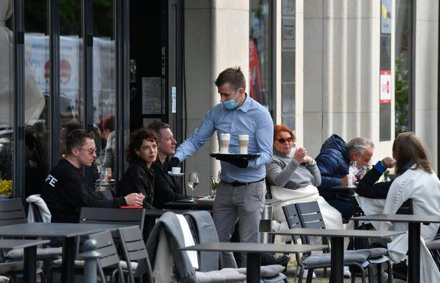 Un serveur apportant des commandes en terrasse dans un café de Berlin, le 15 mai