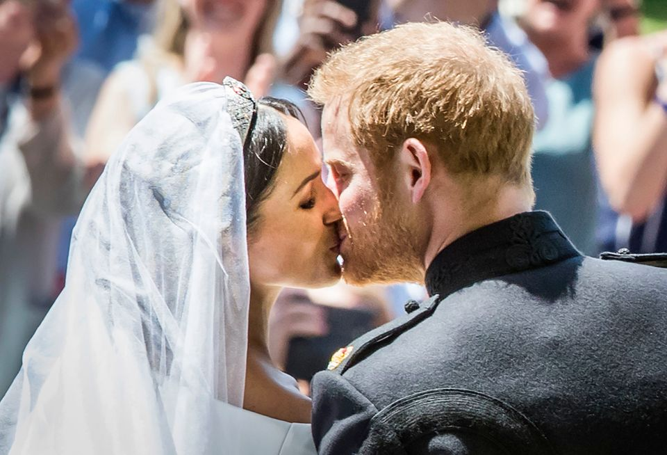 The Duke and Duchess of Sussex kiss as they leave from the West Door of St. George's Chapel after their wedding ceremony.