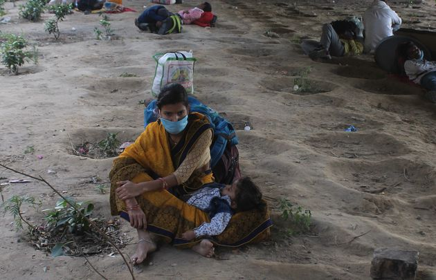 Stranded migrant workers rest under the Rajiv Chowk flyover while on a journey back home to another state,...