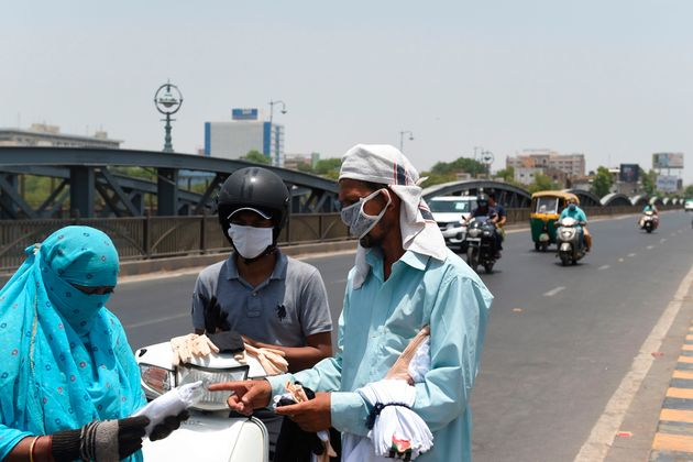 A vendor sells facemasks and hand gloves to commuters along a road in Ahmedabad on May 16,