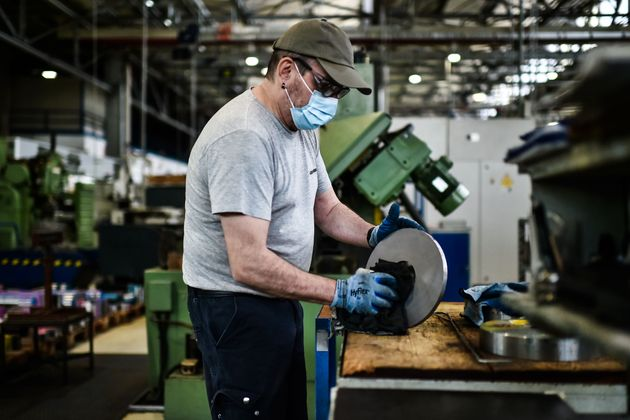 An employee wearing a face mask and gloves works at the multinational equipment manufacturer Liebherr...