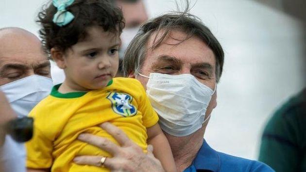 Jair Bolsonaro cogiendo en brazos a una niña, sin respetar la distancia