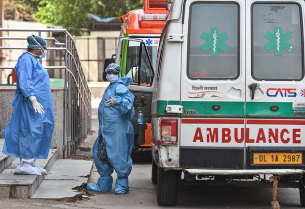 An ambulance driver (R) in PPE coveralls interacts with a medial worker outside the Covid-19 ward, at...