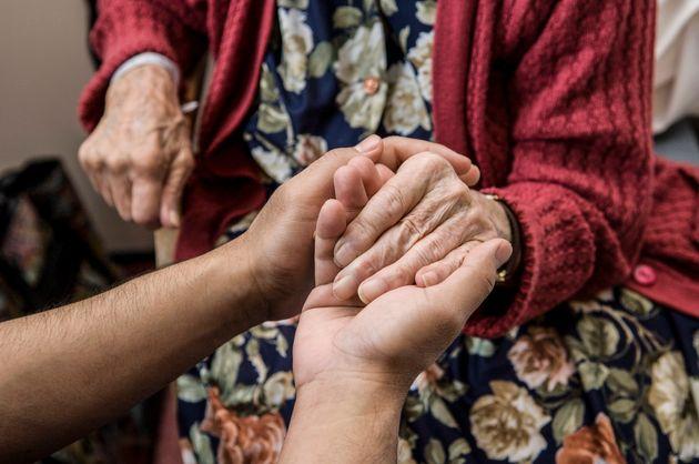 Nurse holding hands with elderly