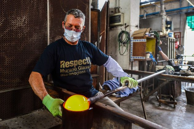A craftsman handles blown glass at the Nason and Moretti glass art products manufacturer on May 18, 2020...
