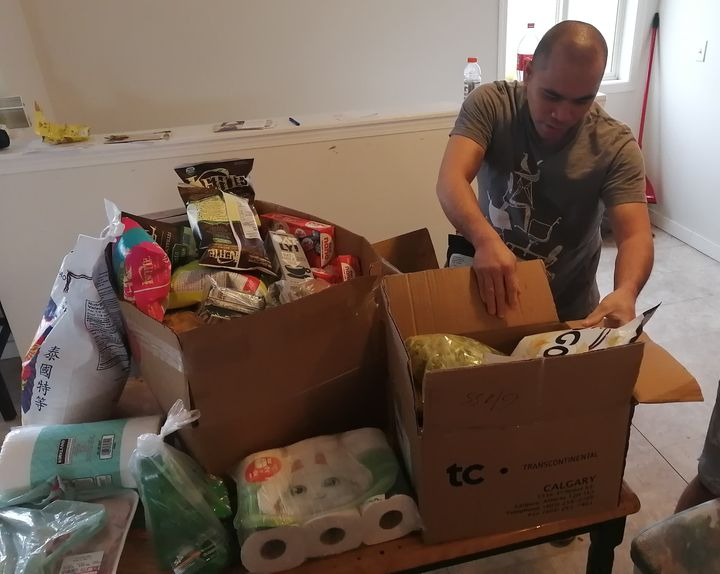 One of Miranda's roommates unpacks toilet paper and food donations, arranged by grassroots group Migrante Alberta.