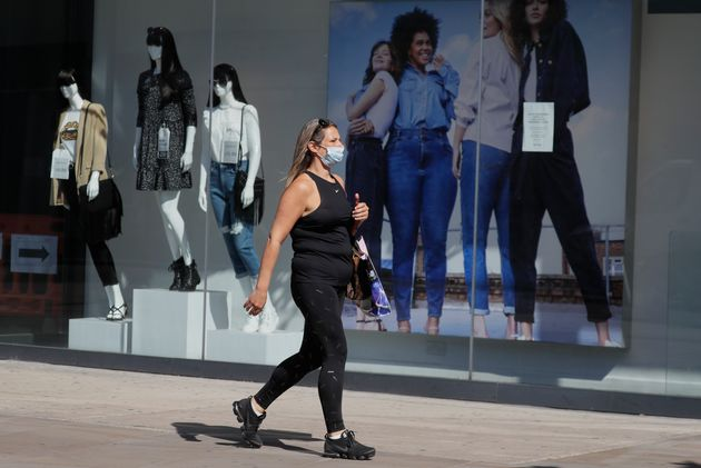 A woman passes a clothing shop in London as the country prepares to lift lockdown