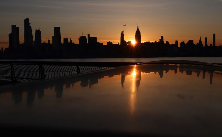 The sun rises behind the Empire State Building and Hudson Yards in New York City on May 14 as seen from Hoboken, New Jersey.