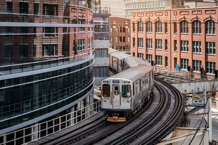 """A commuter train moving on elevated tracks between buildings in Chicago. The New York Times calls public transit """"an infrastr"""