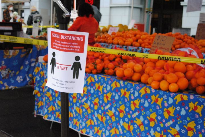Caution tape prevents shoppers from touching the produce at the Ferry Plaza Farmers Market in San Francisco.