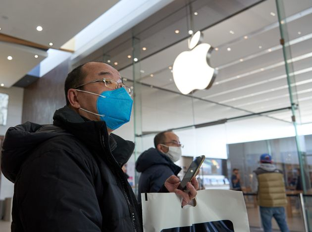 Customers wait outside an Apple store in Montreal on March 15, 2020. Twelve retail locations are reopening...