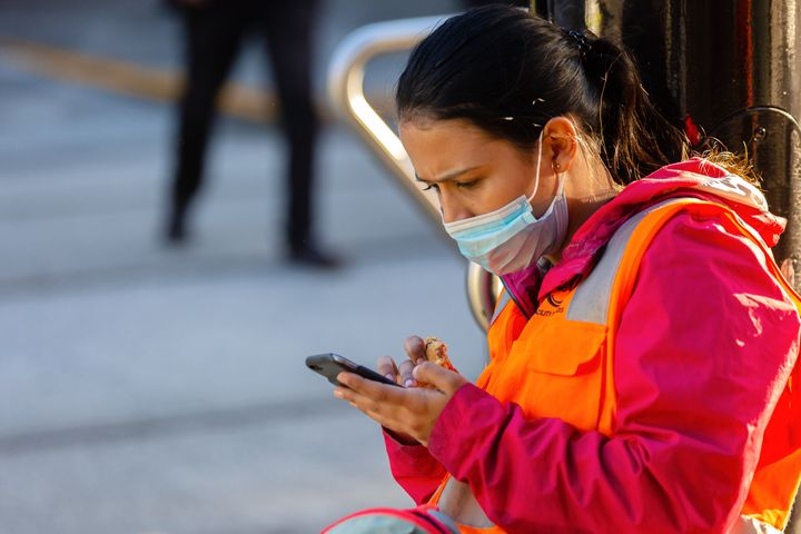 A woman wearing a face mask uses her phone during the coronavirus pandemic on May 16 in Melbourne, Australia. (Photo by Speed
