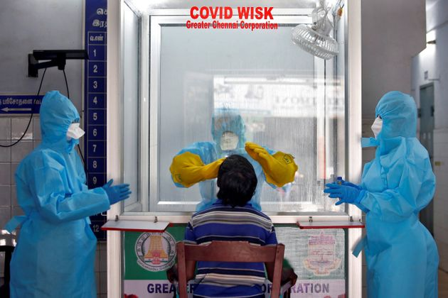 A doctor in a protective chamber takes a swab from a man to test for coronavirus disease (COVID-19) at...