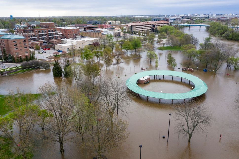 Water floods the Midland Area Farmers Market and the bridge along the Tittabawassee River in Midland, Michigan on Tuesday.