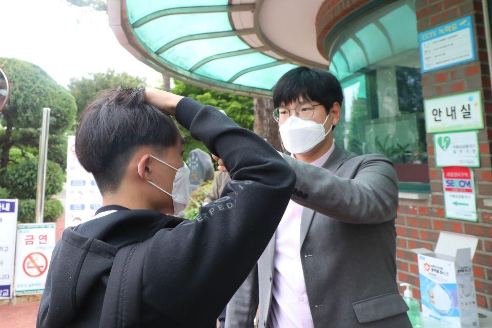 20일 서울 동작구 서울공고에서 고등학교 3학년 학생이 등교하며 체온측정을 받고