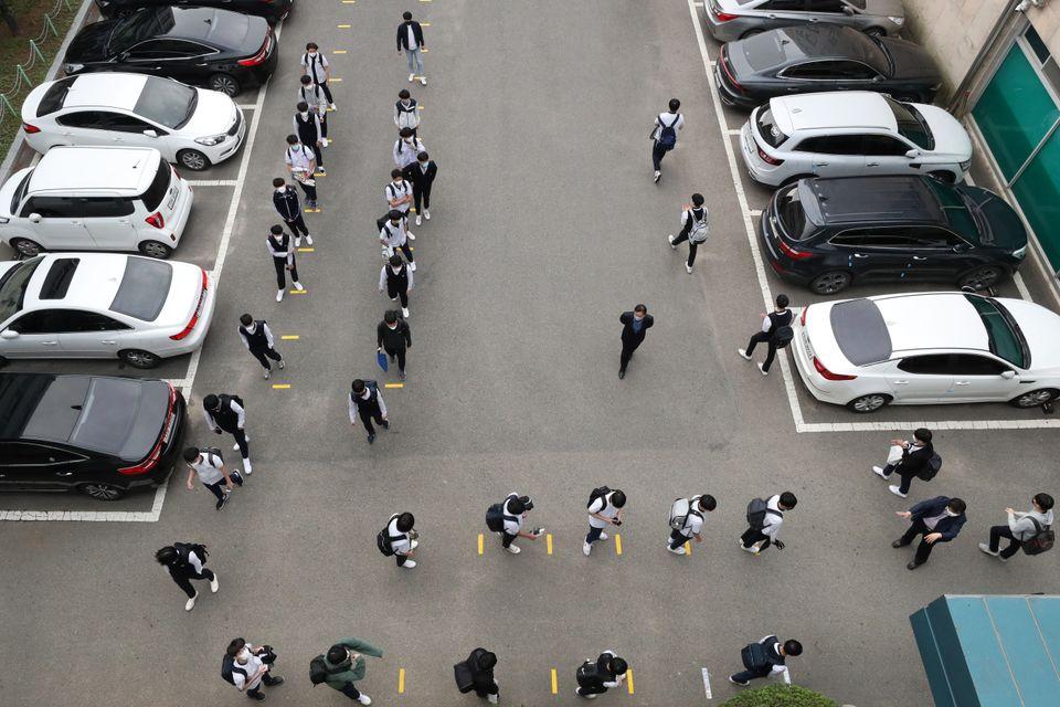 20일 오전 경기도 수원시 팔달구 수원고등학교에서 고3 학생들이 마스크를 쓴 채 등교 전 발열 검사를 받기 위해 거리를 두고 줄 서서 대기하고