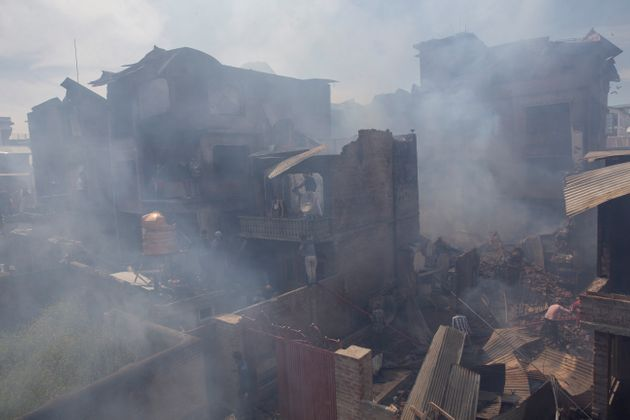 Kashmiri men douse the fire in a house which was destroyed in a gun-battle in Srinagar, Jammu and Kashmir,...
